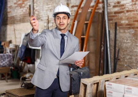 Confident male architect in suit and helmet controlling process of building