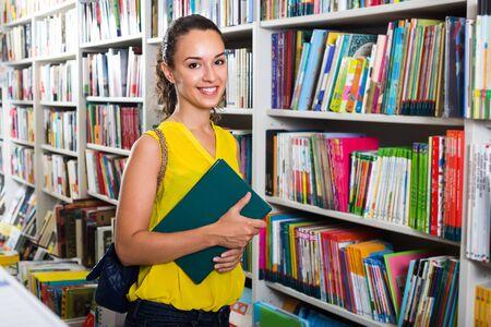 portrait of joyful young brunette woman picking books from shelves in book shop Zdjęcie Seryjne