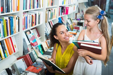 Young smiling woman with girl in school age looking in open book in bookstore