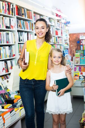 portrait of smiling young mother with little schoolgirl daughter picking textbooks for school in book shop