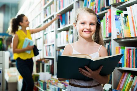Cheerful child in school age looking in open chosen book in shop