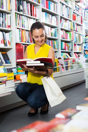 Smiling adult brunette woman looking at book in hard cover in bookstore Zdjęcie Seryjne