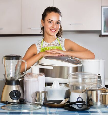 Happy housewife with a kitchen appliances in the home Archivio Fotografico