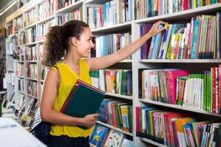 Young smiling woman shopping books in hard cover in bookstore
