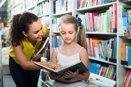 Young positive female with girl  in school age looking in open book in bookstore