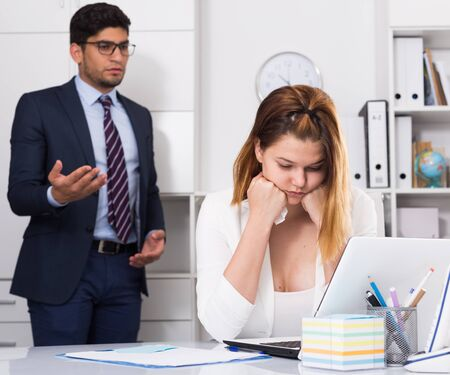 Upset woman sitting at laptop in office with disgruntled boss behind