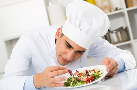 Young man is evaluating prepared dish on kitchen.