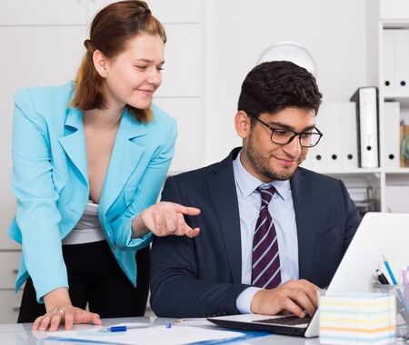 Businessman and businesswoman sitting at desk and working together at office