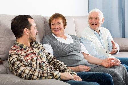 Parents and adult son enjoying quiet evening together at home