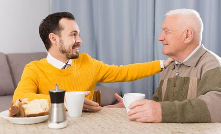 Father and adult son enjoying quiet evening together at home