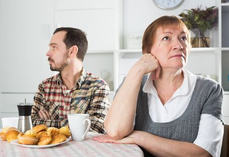 Elderly mother resents her son at table at home Stock fotó