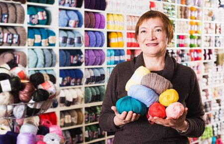 Smiling woman posing with yarn for knitting in needlework store