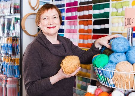Glad cheerful positive smiling mature woman buying colorful yarn for their hobby on special offers