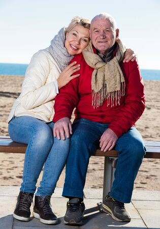 Aged husband and wife sitting together on bench by sea on chilly day Stock fotó