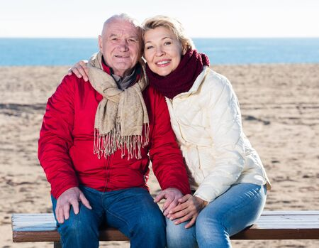 Senior couple sitting on bench and embracing on beach by sea