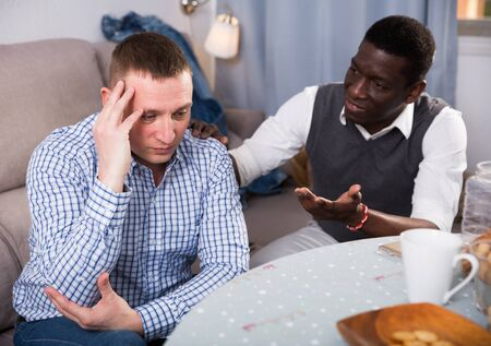 Offended adult man sitting at home table while his African American friend soothing him