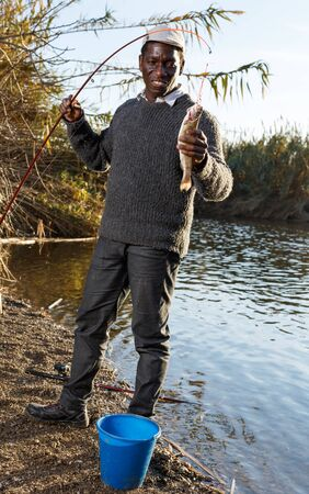 Portrait of afro fisherman holding fishing rod with fish on hook