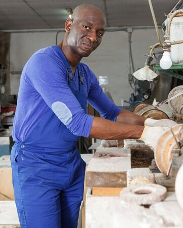 Serious African American glass factory worker engaged in adjustment of equipment Stock fotó