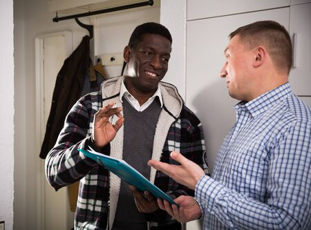 Smiling adult man participating in survey conducted at home by polite social worker