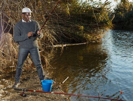 Portrait of positive African man standing with fishing rod near river Reklamní fotografie