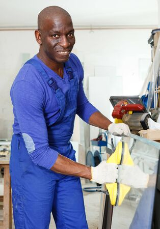 Portrait of confident African-American man in blue overalls working in glass workshop