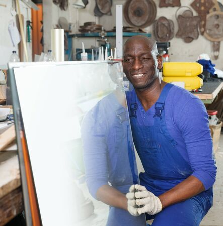 African-American workman working with glass in workshop