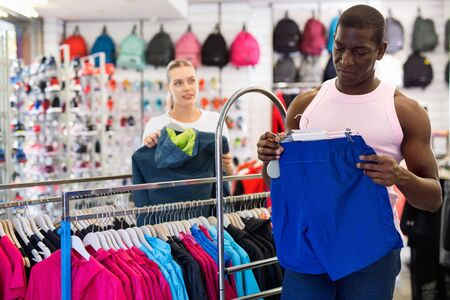 Portrait of cheerful positive smiling African American man choosing shorts in sporting goods store