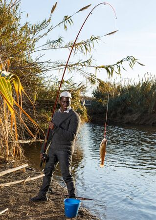 Portrait of enthusiastic African man holding fishing rod with fish on hook