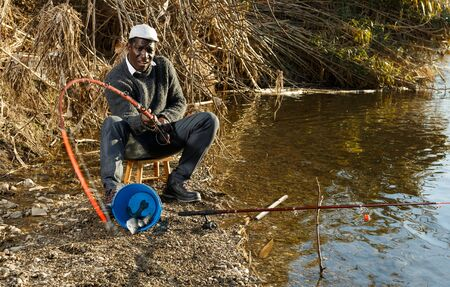 Portrait of enthusiastic African man pulling fish with rods on river Reklamní fotografie