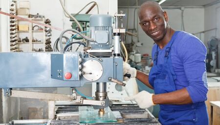Confident African American glazier working with glass on stationary drilling machine in workroom