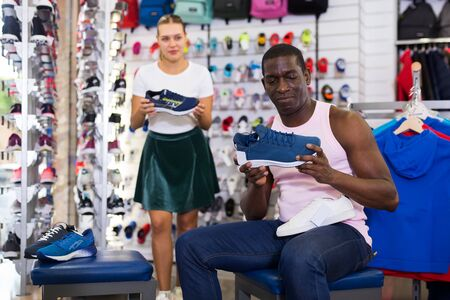 African American man customer trying sports shoes in sporting goods shop
