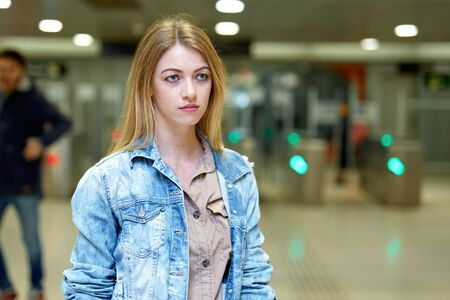Blonde with long hair stands near the turnstiles at subway station Stok Fotoğraf