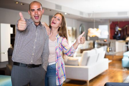 Husband and wife are giving thumbs up as sign of successful purchase new furniture. 스톡 콘텐츠 - 133949714