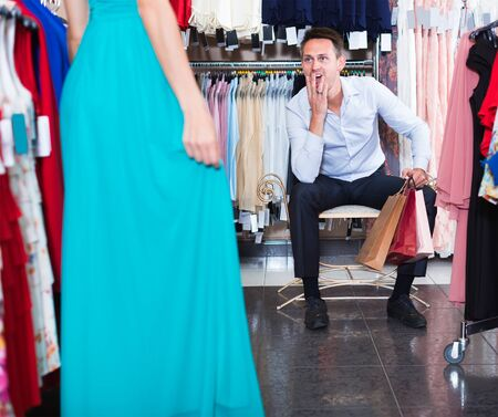 pair of young friendly people in women clothes boutique choose dresses