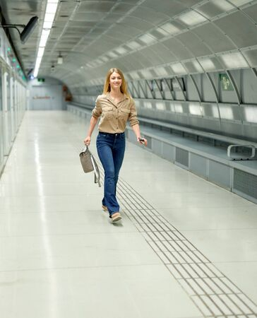 Slender young girl goes on the subway platform Stok Fotoğraf