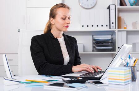 Jeune femme d'affaires souriante en costume remplissant des documents Banque d'images