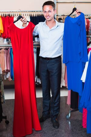 Portrait of young smiling man offering to girlfriend dress variants in the womens clothing store