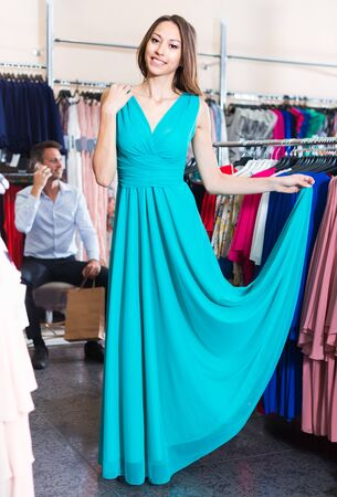 Young cheerful female is trying on new blue dress in boutique.