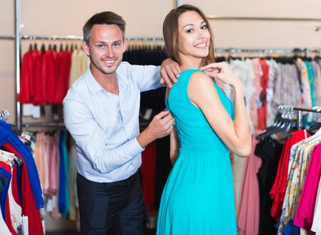Portrait of family couple choosing new dress in women clothes shop