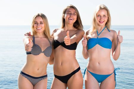 three joyful smiling attractive girls looking happy in bikini on beach