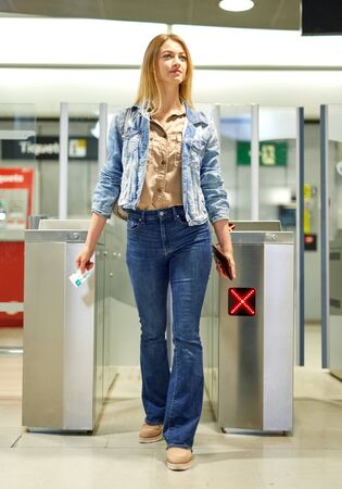 Blonde with long hair passing the turnstiles at subway station Stok Fotoğraf - 133951980