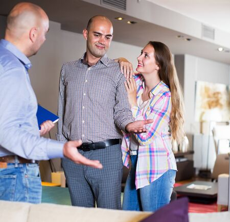 Family couple choosing furniture for apartment in store with help of salesman 스톡 콘텐츠