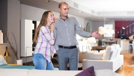 Cheerful couple choosing furniture for apartment in modern home furnishings store