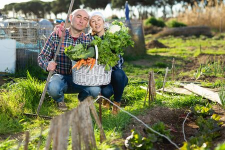 Joyful couple with a basket of vegetables in the garden