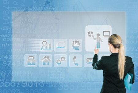 Business lady touching digital interface with finger on industrial business background