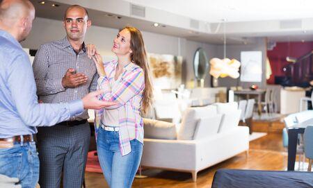Coppia di famiglia che sceglie mobili per appartamento nel negozio di mobili per la casa con l'aiuto del venditore