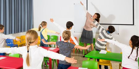 Young friendly female teacher conducting little warm-up with pupils during  break in lesson in elementary school Banco de Imagens