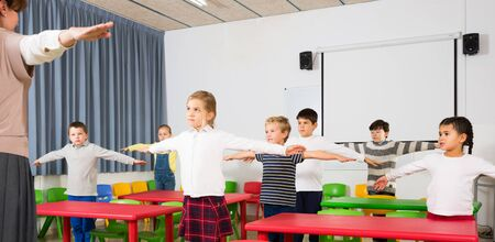 Portrait of schoolchildren with teacher performing daily physical exercises in classroom during break on lesson Banco de Imagens