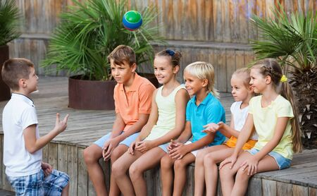 Cheerful smiling positive boys and girls in school age sitting and playing with ball outdoors Zdjęcie Seryjne