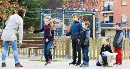 happy european children playing rubber band jumping game and laughing outdoors Zdjęcie Seryjne